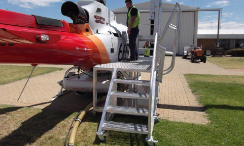 Custom built helicopter platform in use as man maintains helicopter on tarmac.