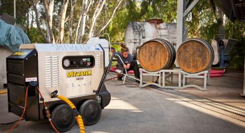 Spitwater pressure cleaner cleaning a set of wine barrels.