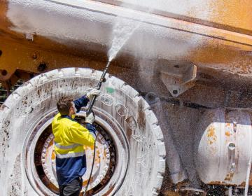 Operator using a Spitwater Pressure Cleaning Foaming a CAT Truck