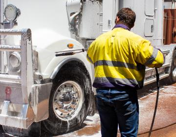 man using foamer to clean front of truck